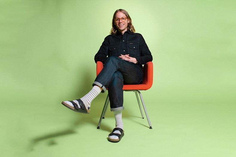 porträtt av erik sittande på stol mot grön bakgrund