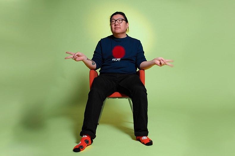 porträtt av nikkie sittande på stol mot grön bakgrund