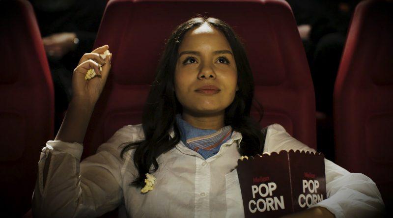 Kvinna i biosalong med popcorn