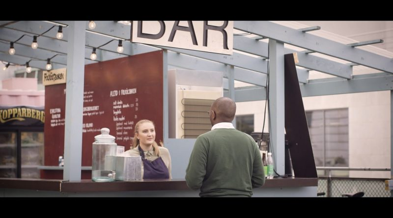 man i grön tröja får hjälp av blond kvinna vid bardisk