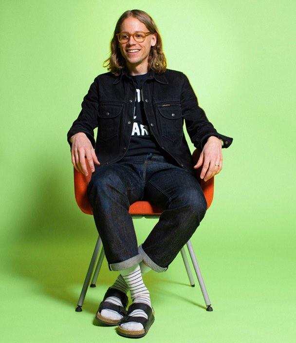 porträtt av erik sittande på en stol mot grön bakgrund
