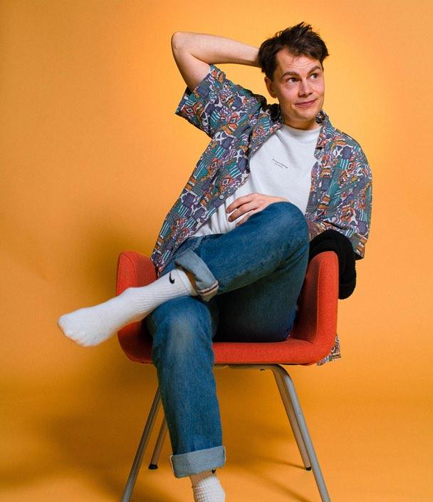 porträtt av viktor sittande på stol mot orange bakgrund