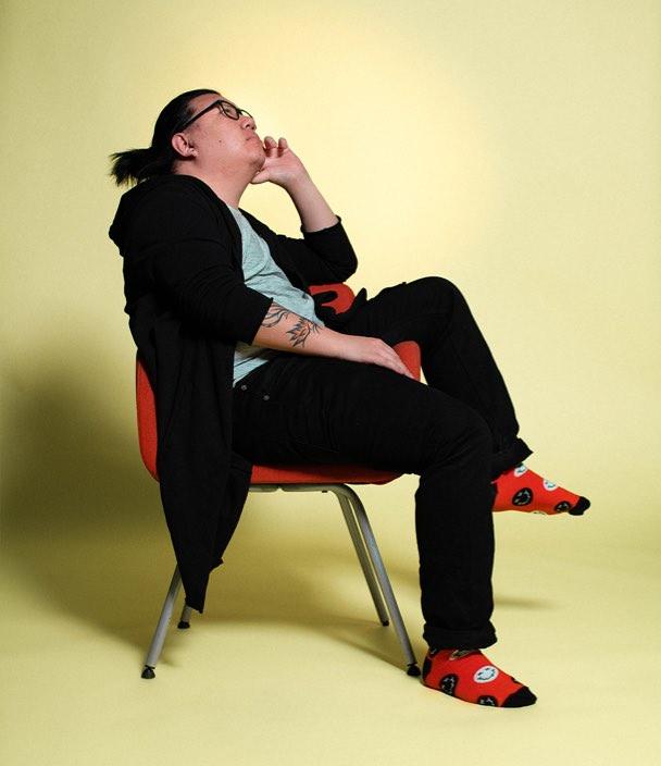 porträtt av Nikkie sittande på en stol mot gul bakgrund