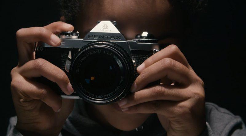 närbild på händer som håller i en kamera